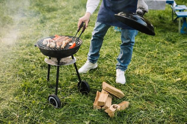 Man met een barbecue in de natuur