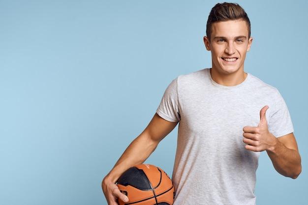 Man met een basketbalbal op een blauw sportspel model witte t-shirt energie.