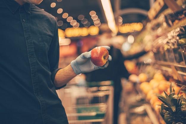 Man met een beschermend masker bij het selecteren van appels in de supermarkt. hygiëne en gezondheidszorg