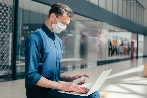 Man met een beschermend masker desinfecteert zijn laptop. pandemie in de stad