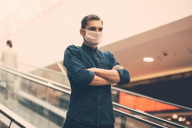 Man met een beschermend masker die op de trappen van de metroroltrap staat