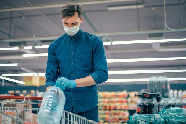 Man met een beschermend masker die water koopt in een supermarkt. foto met een kopie-spatie