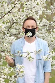Man met een beschermend masker met bloeiende bomen