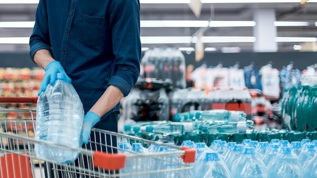 Man met een beschermend masker met een winkelwagentje dat op de handelsvloer staat. foto met een kopie-spatie