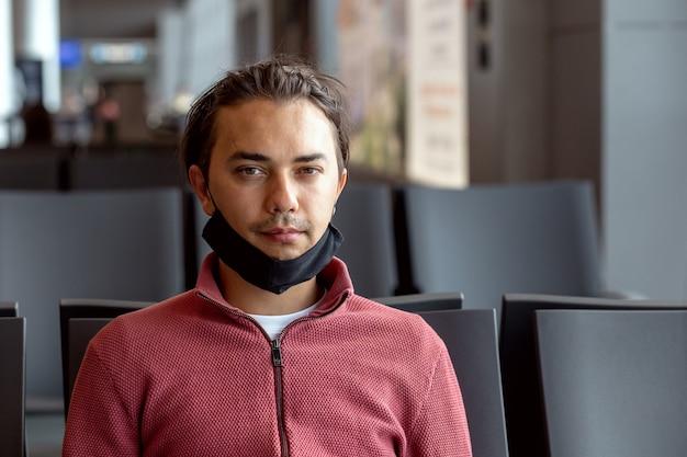 Man met een beschermend zwart medisch masker op het gezicht op de luchthaven wacht op de vlucht.