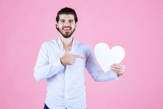 Man met een blanco hartfiguur en erop wijzend.