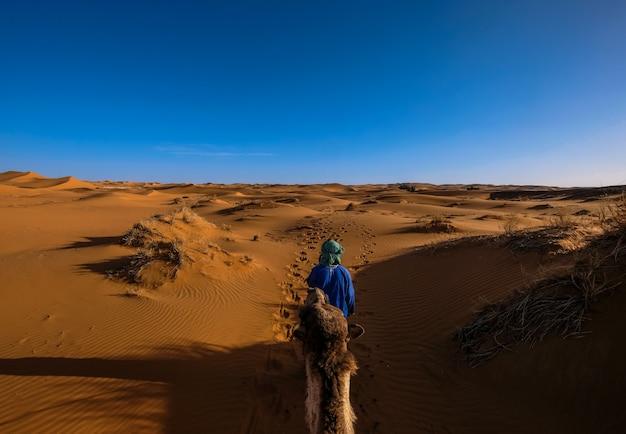 Man met een blauw shirt lopen voor een kameel in het midden van zandduinen met heldere hemel