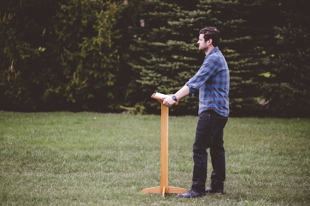 Man met een blauw shirt staande in de buurt van de houten podium