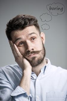 Man met een blauw shirt ziet er verveeld uit. over grijze achtergrond