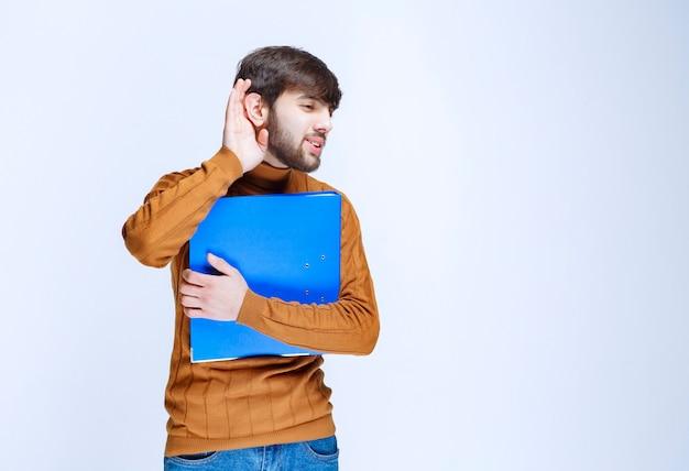 Man met een blauwe map die aandachtig luistert.