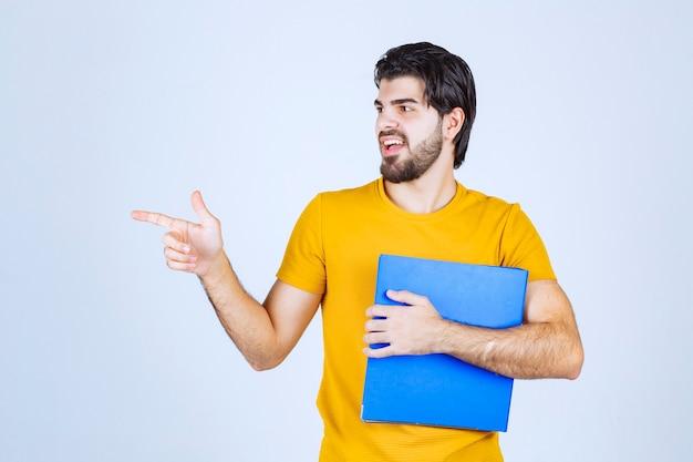 Man met een blauwe map die zijn collega aan de linkerkant wijst en met emoties praat.