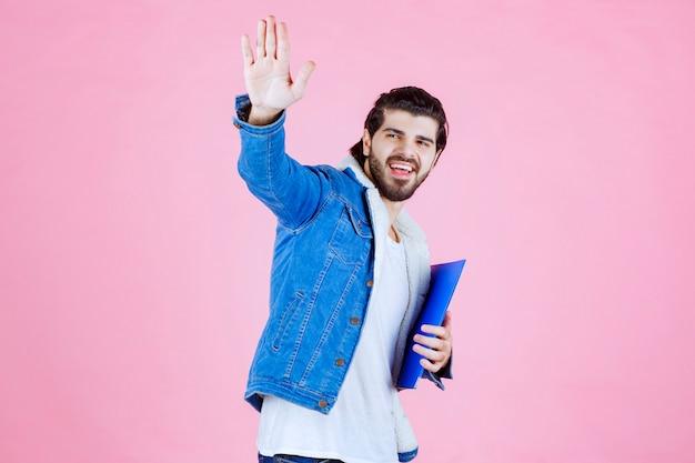 Man met een blauwe map die zijn collega's begroet