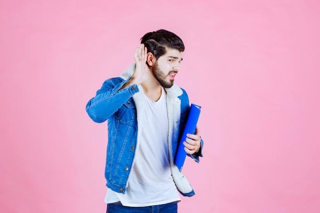 Man met een blauwe map die zijn oor wijst omdat hij niet goed kan horen