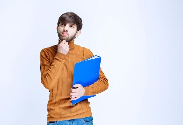 Man met een blauwe map kijkt verward en doodsbang.