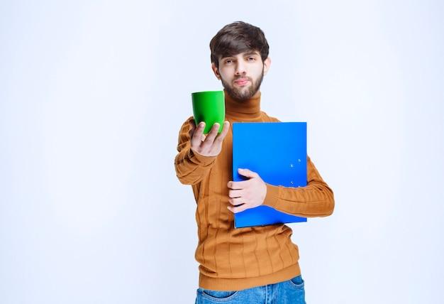 Man met een blauwe map met een groene kop drank.