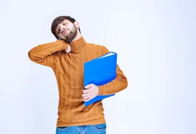 Man met een blauwe map ziet er moe en slaperig uit.