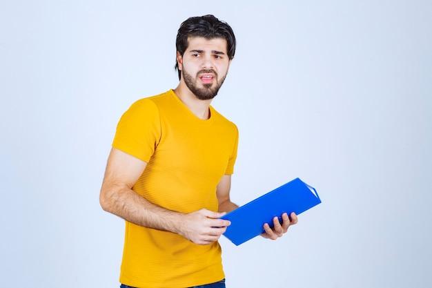 Man met een blauwe map ziet er verward of onervaren uit.