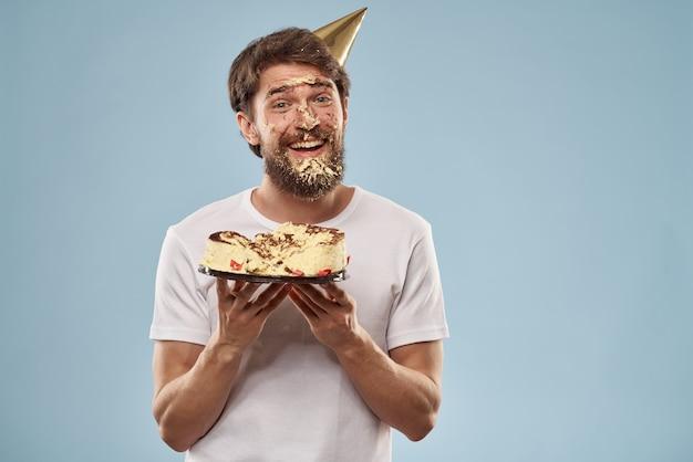 Man met een bord met cake in een feestmuts
