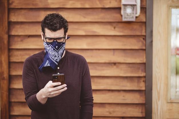 Man met een bril en een sjaal als gezichtsmasker met zijn telefoon voor een houten muur