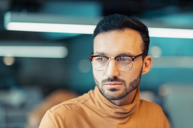 Man met een bril. knappe volwassen donkerharige man met een bril en een oranje polohals