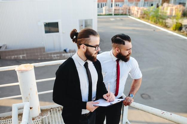 Man met een bril te kijken naar een tablet met een andere man op de achtergrond