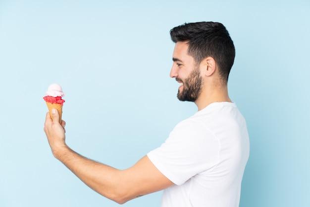 Man met een cornet-ijs geïsoleerd op blauw met gelukkige uitdrukking
