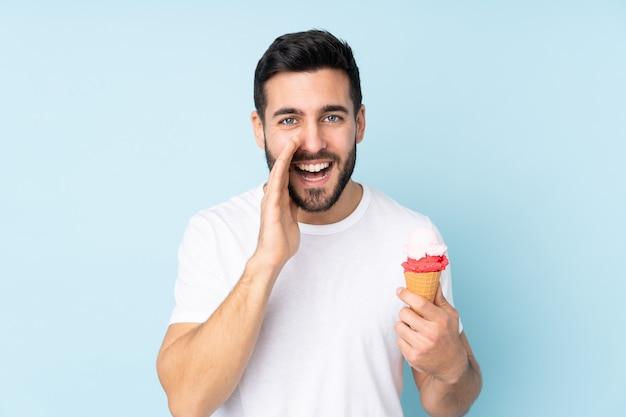 Man met een cornet-ijs geïsoleerd op blauw schreeuwen met wijd open mond
