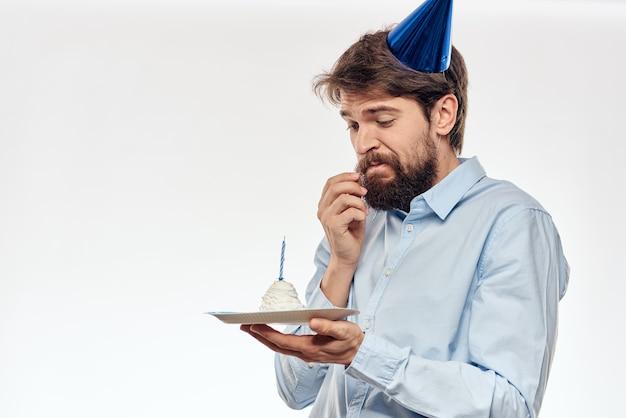 Man met een cupcake en een kaars in een feestmuts