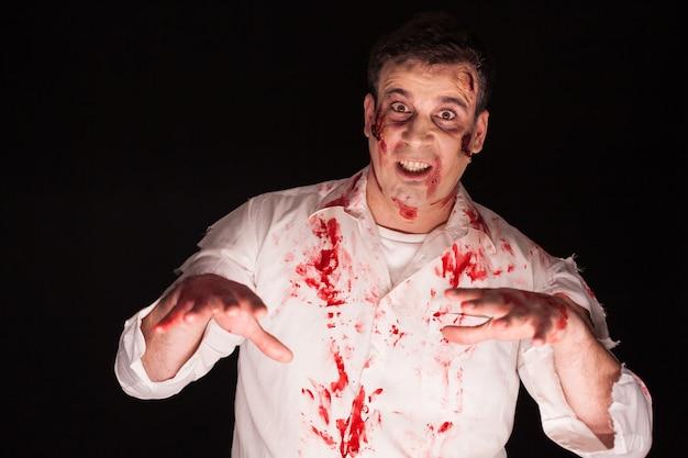 Man met een demon in zijn lichaam en bloed geïsoleerd op zwarte achtergrond. halloween creatieve make-up.