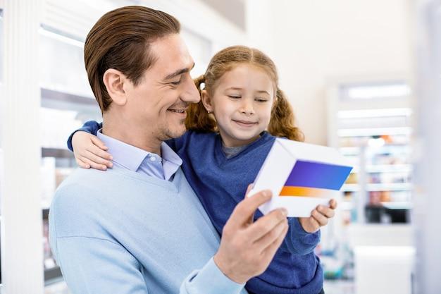 Man met een dochtertje in zijn armen die haar medicijn toont, beide vrolijk