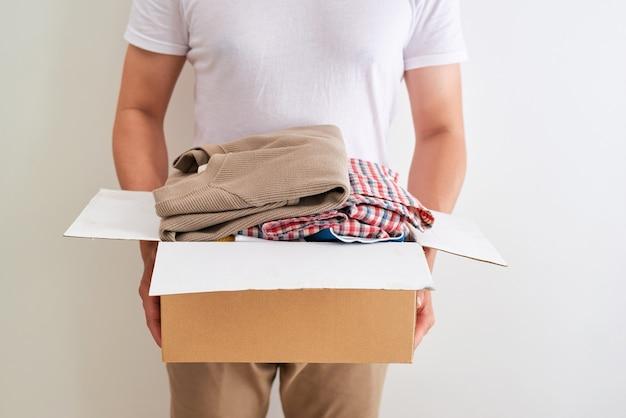 Man met een doos voor het doneren van kleding. donatie concept.