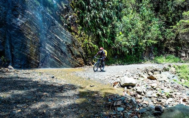 Man met een fiets op de zonneschijn van boliviaanse doodsweg in de buurt van enorme rots met waterval