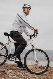 Man met een fiets op een koude dag