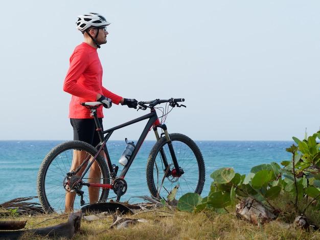 Man met een fiets staat op de oceaan kust