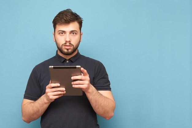 Man met een gadget in zijn hand is geïsoleerd op blauw