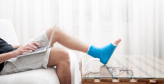 Man met een gebroken been in blauwe spalk voor behandeling van blessure en enkelverstuiking gebruikt thuis een laptop.