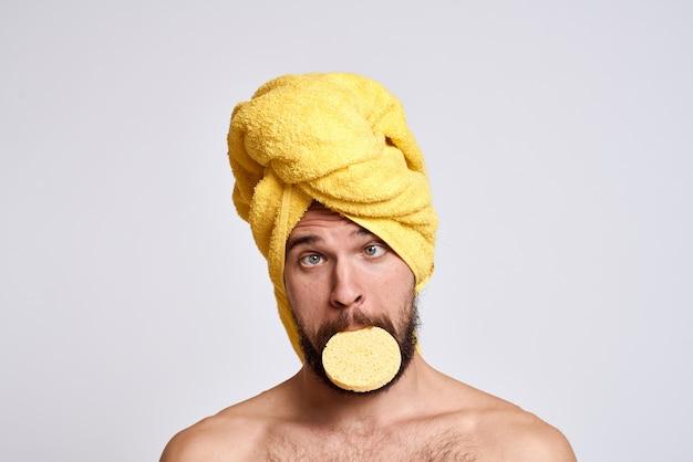 Man met een gele handdoek op zijn hoofd blote schouders spons schone huid gezichtsverzorging lichte achtergrond. hoge kwaliteit foto