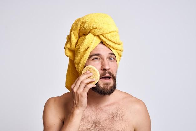Man met een gele handdoek op zijn hoofd blote schouders spons schone huid gezichtsverzorging lichte ruimte.