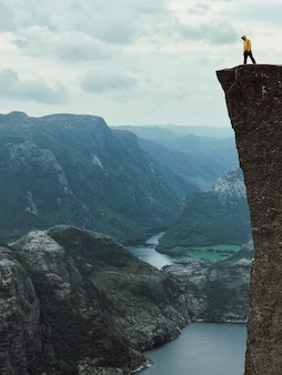 Man met een gele jas staat op de top van de rots