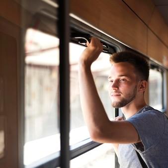 Man met een gemiddelde shot die uit het raam kijkt
