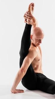 Man met een gemiddelde shot die zijn been vasthoudt