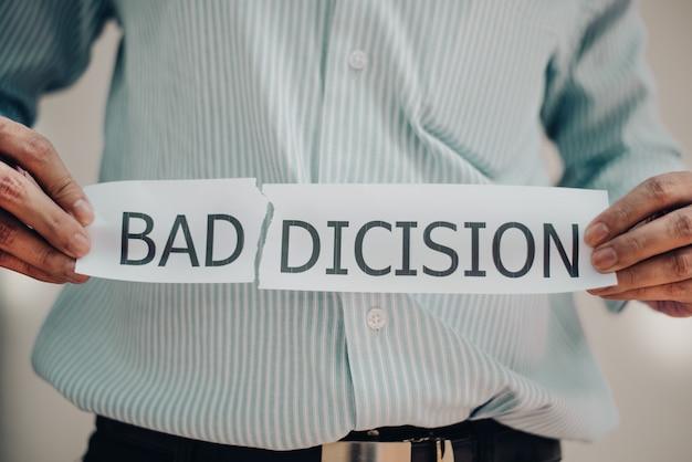 Man met een gescheurd papier handen met de woorden: slechte discisie, zelfontwikkelingsconcept