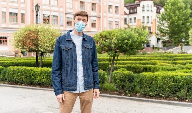 Man met een gezichtsmasker buiten met kopie ruimte