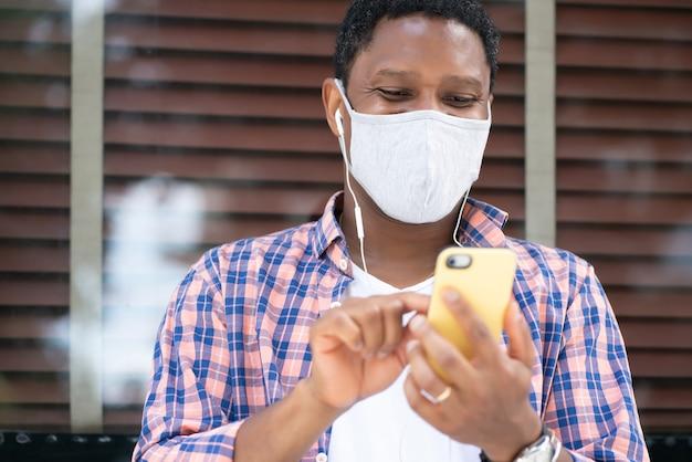 Man met een gezichtsmasker en met behulp van zijn mobiele telefoon zittend bij een etalage op straat.