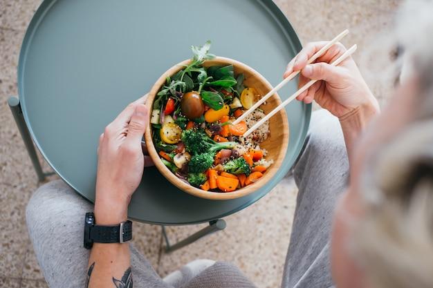 Man met een gezonde levensstijl en groene voedselkeuzes eet verse en heerlijke buddha bowl-schotel met voedingsstoffen en eiwitten