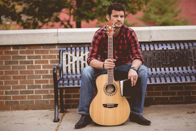 Man met een gitaar en een boek zittend op een bankje in het park onder zonlicht