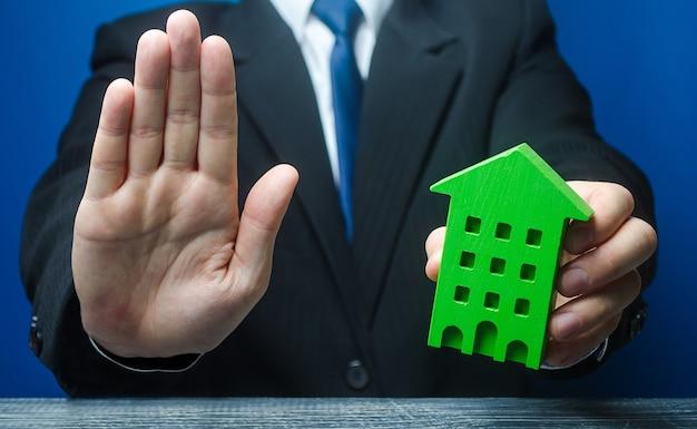 Man met een groen huis maakt een stopgebaar.