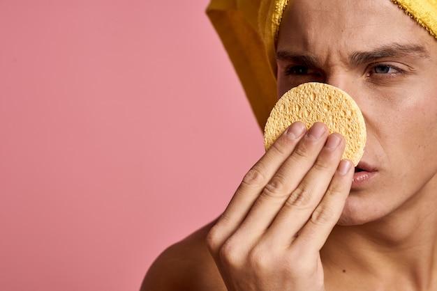 Man met een handdoek op zijn hoofd en een gele spons in zijn hand cosmetische procedure schone huid van het gezicht.