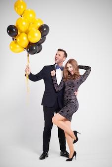 Man met een heleboel ballonnen omhelst vrouw