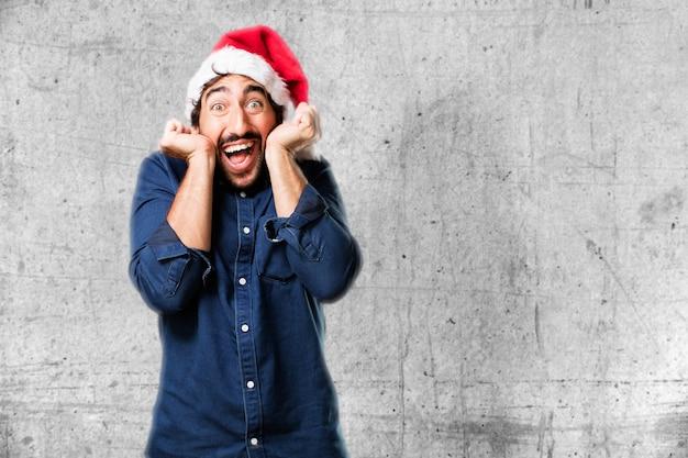 Man met een hoed santa verrast met de handen op het gezicht